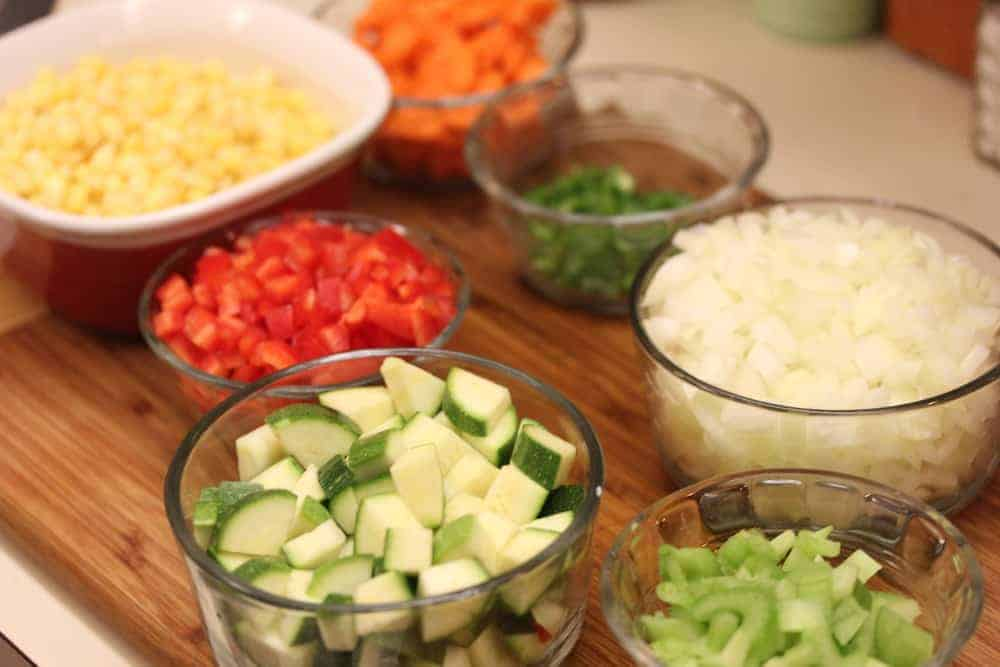 Glass bowls holding a variety of vegetables for vegetable and black bean chili.