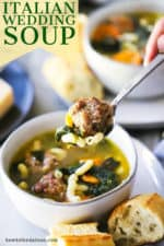 A hand holding a soup spoon with a meatball, some pasta, and spinach on it and over a bowl of the soup.