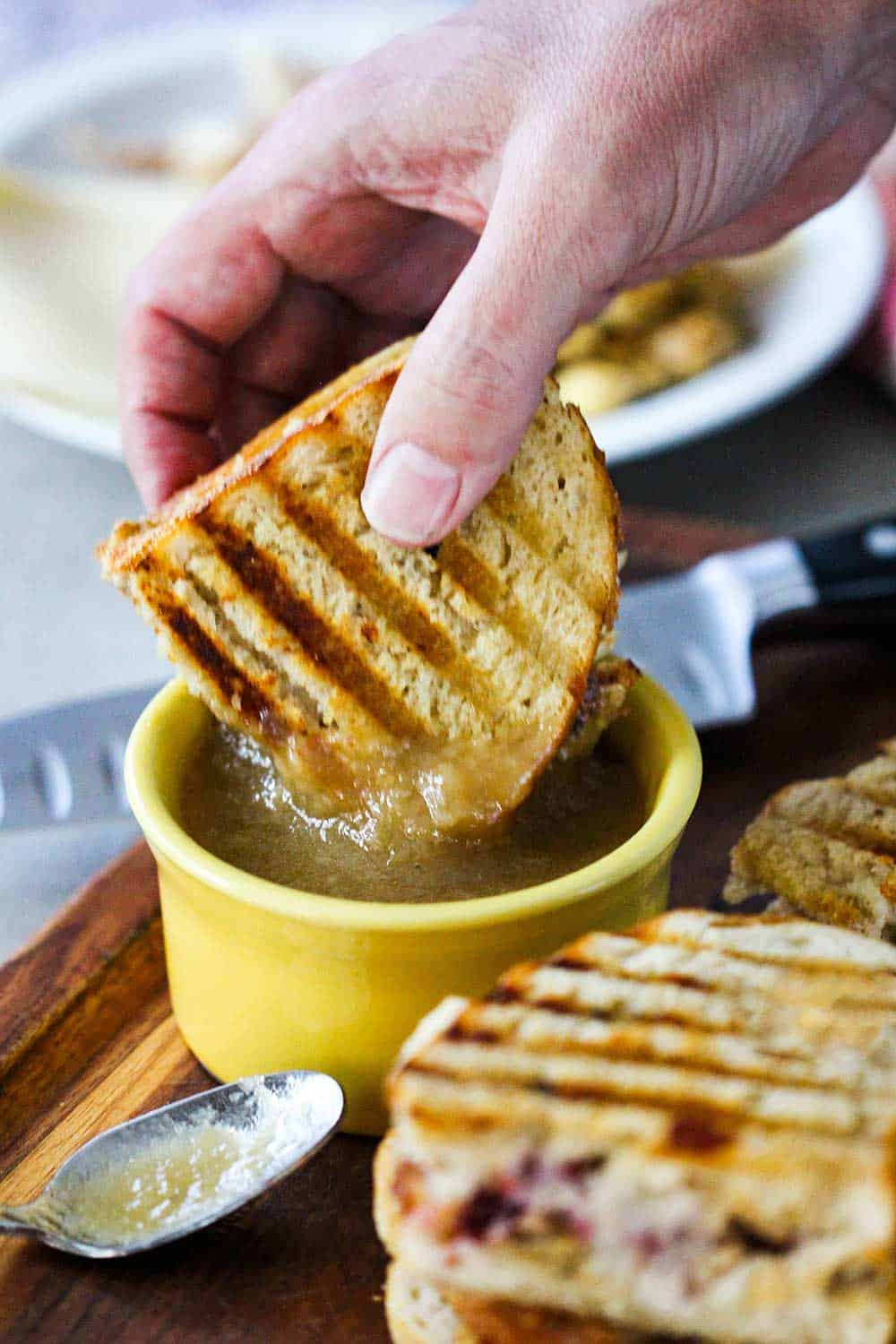 A hand dipping a Day After Thanksgiving Panini into a bowl of gravy.