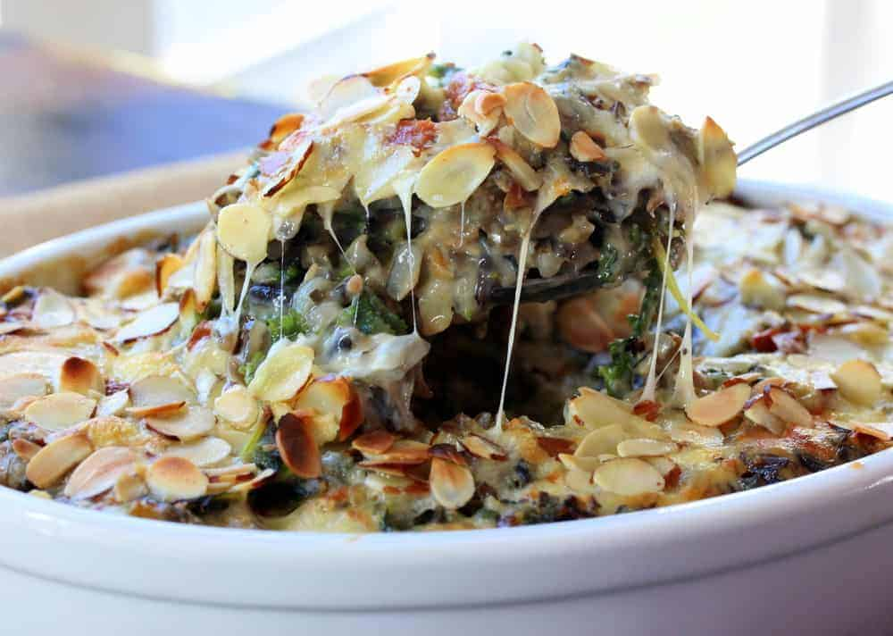 A spoon lifting our a helping of Wild rice, kale, and fontina casserole in a white dish.
