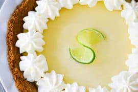 An overhead view of a key lime pie in a white pie dish with whipped cream puffs along the edge of the pie.