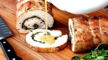 Herb Stuffed Pork Loin on a wood cutting board being drizzled with gravy