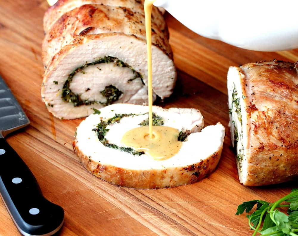 A sliced herb-stuffed pork loin on a cutting board next to a chef's knife with gravy being poured on it from a white gravy boat.