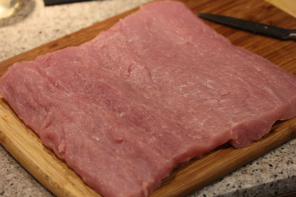 A large flat piece of pork loin that has been butterflied on a wooden cutting board.