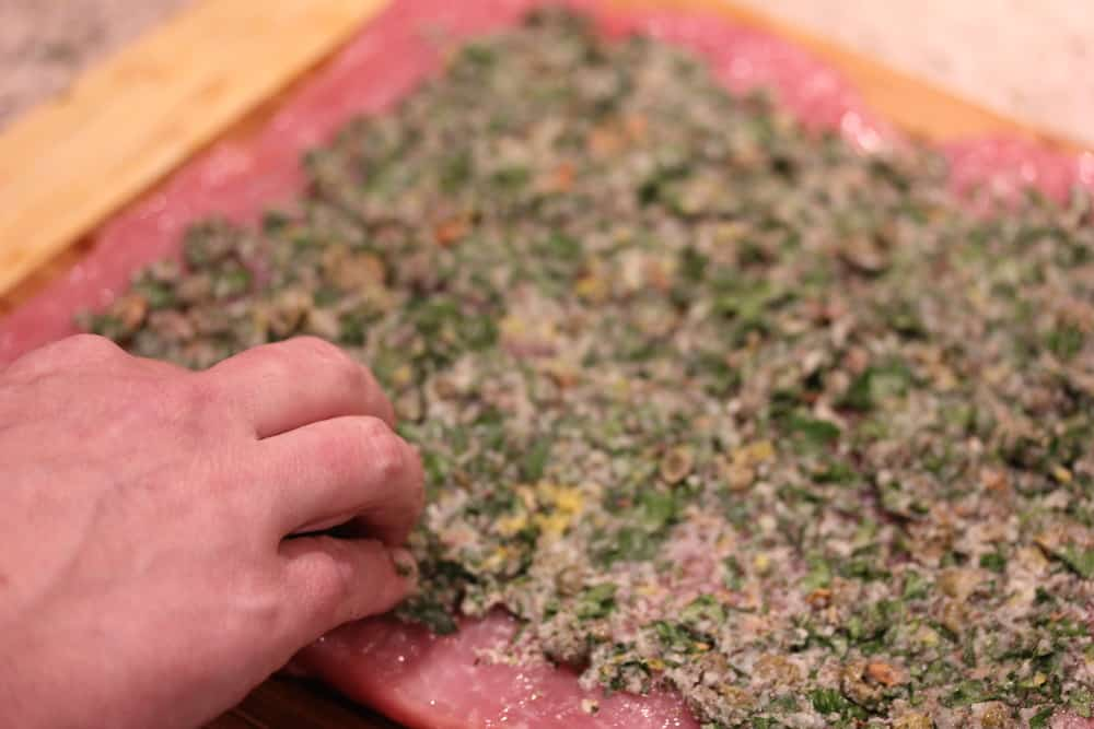 A hand spreading an herb filling all over the top of a butterflied pork loin.