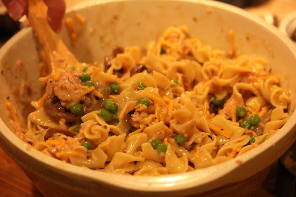 A bowl filled with cooked pasta, peas, mushrooms, and tuna for gourmet tuna casserole with a large spoon in it.