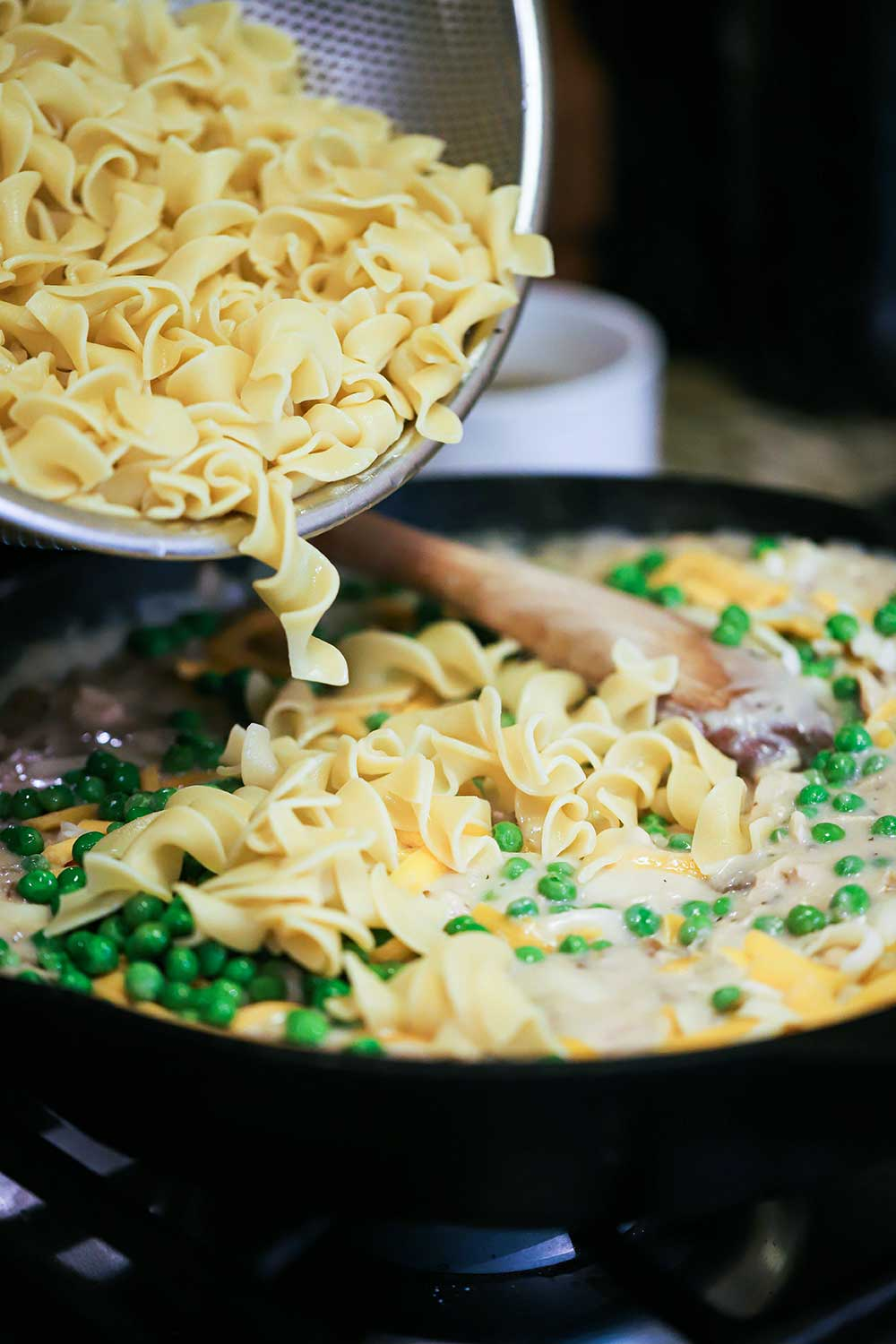 Cooked extra-wide egg noodles being transferred into a large cast-iron skillet filled with cream of mushroom soup, peas, and shredded cheese.