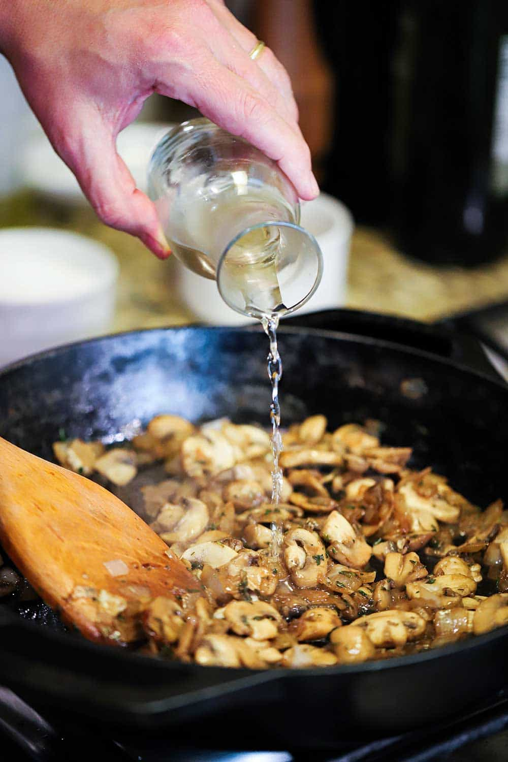 A hand pouring white wine from a small carafe into a cast-iron skillet filled with sautéd sliced mushrooms.