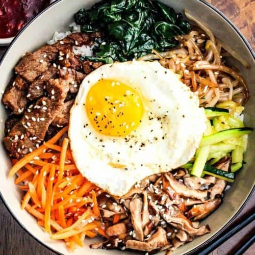 Authentic Bibimbap in a bowl with Korean BBQ sauce and chop sticks