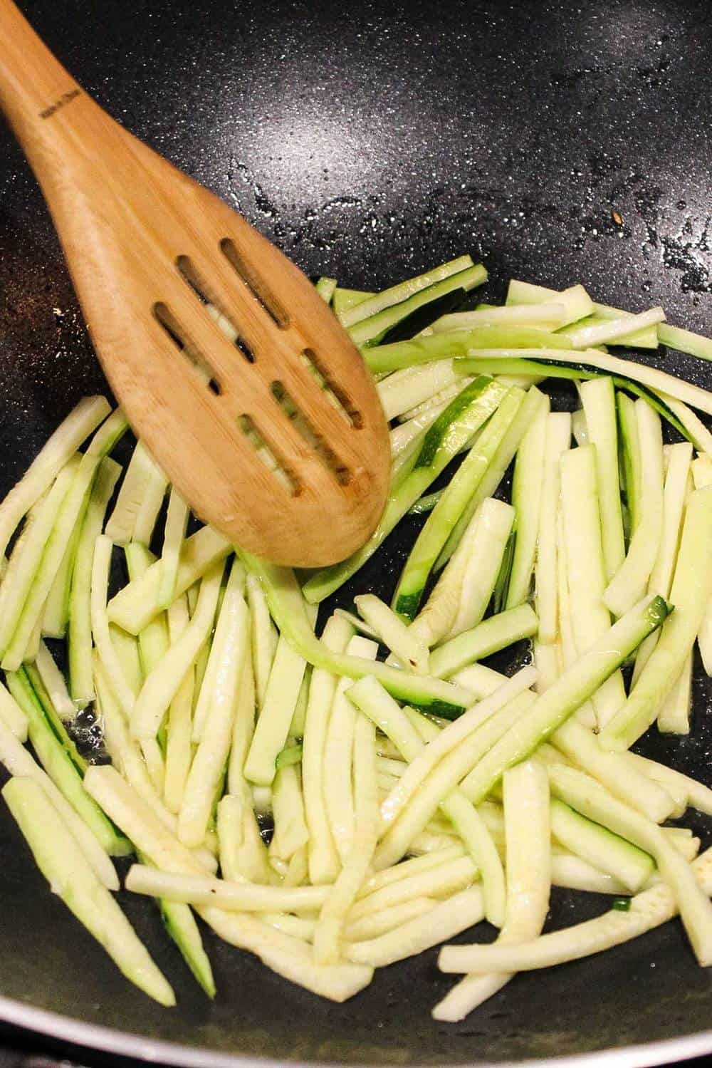 Shredded zucchini being stir fried in a wok for bibimbap