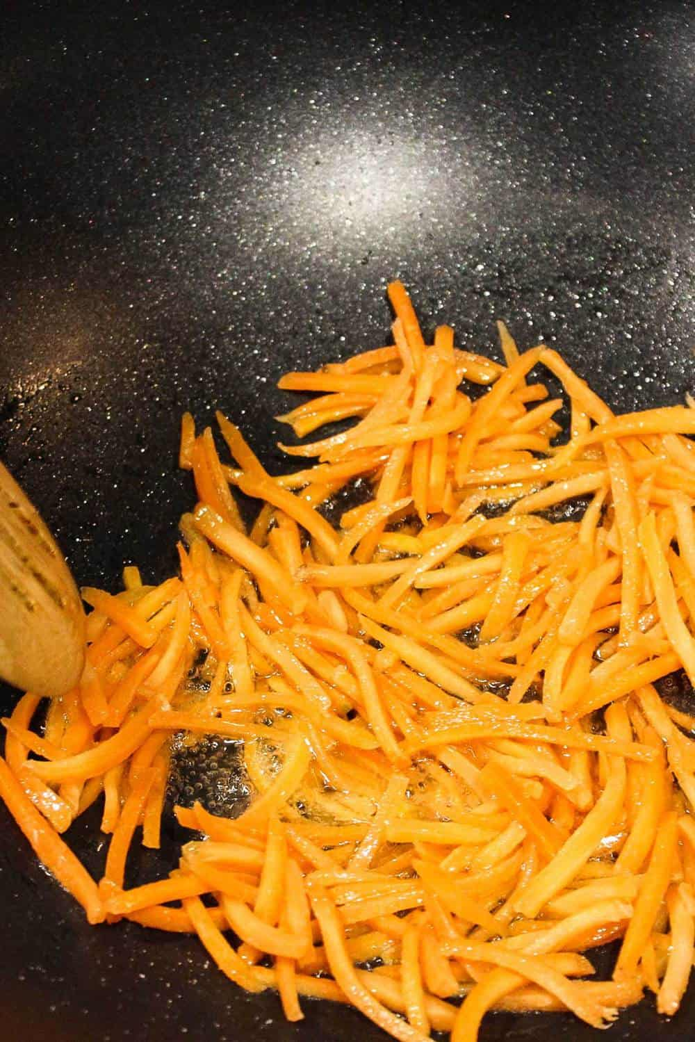 Shredded carrots being stir fried in a wok for bibimbap