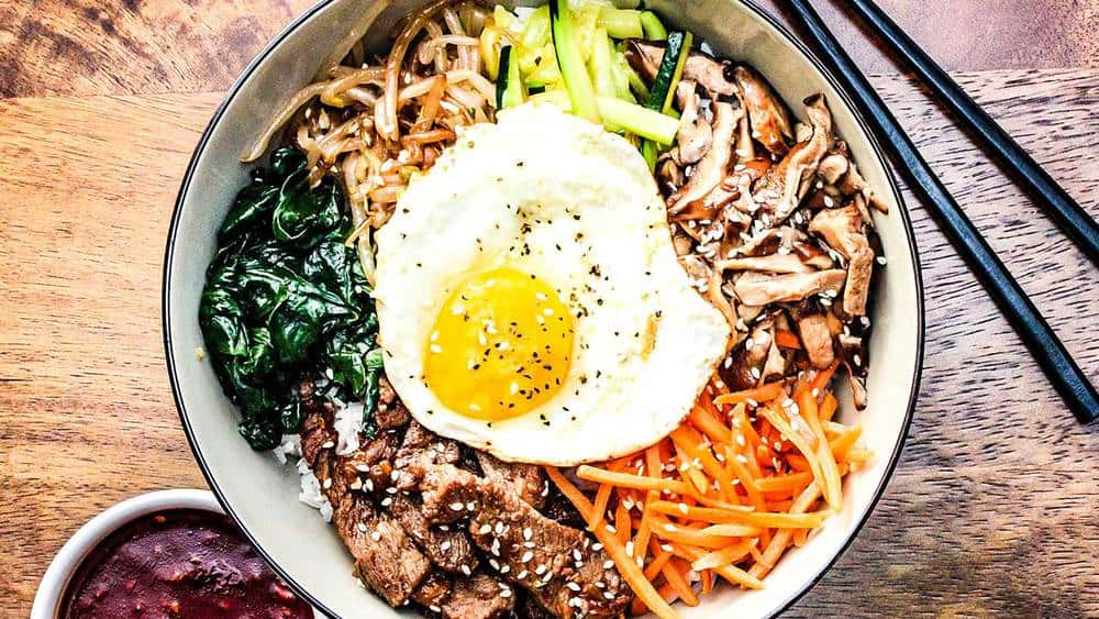 A bowl of authentic bibimbap next to Korean BBQ sauce and chop sticks