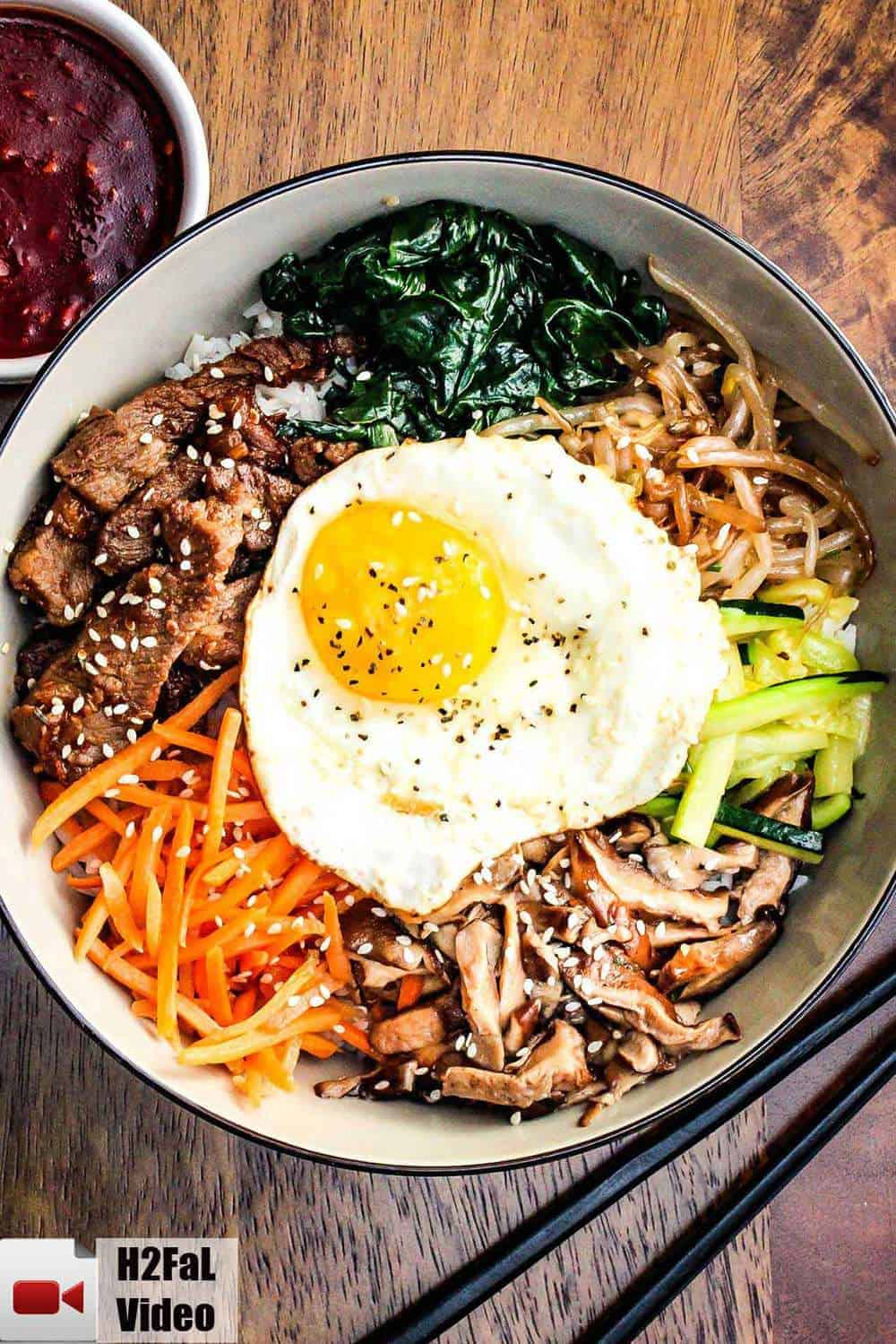 Authentic bibimbap in a bowl next to chop sticks