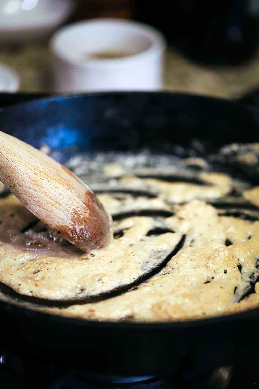 A wooden spoon stirring a blonde roux in a large black cast-iron skillet.