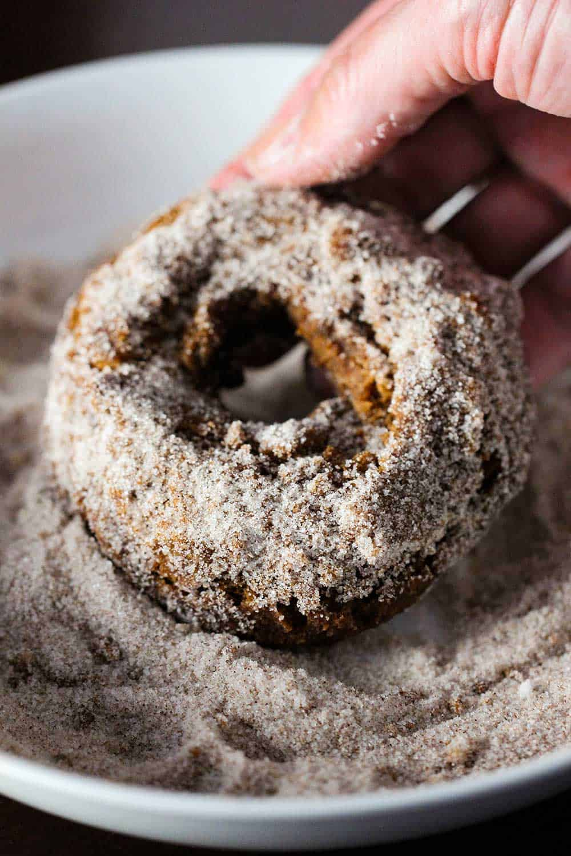 A hand dredging an apple cider doughnut in a bowl of a cinnamon sugar mixture.