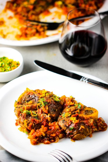 A white plate with the dish Osso Buco on it next to a glass of red wine