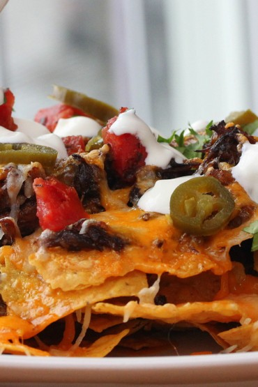 A white platter with Braised Ancho Chili Short Rib Nachos