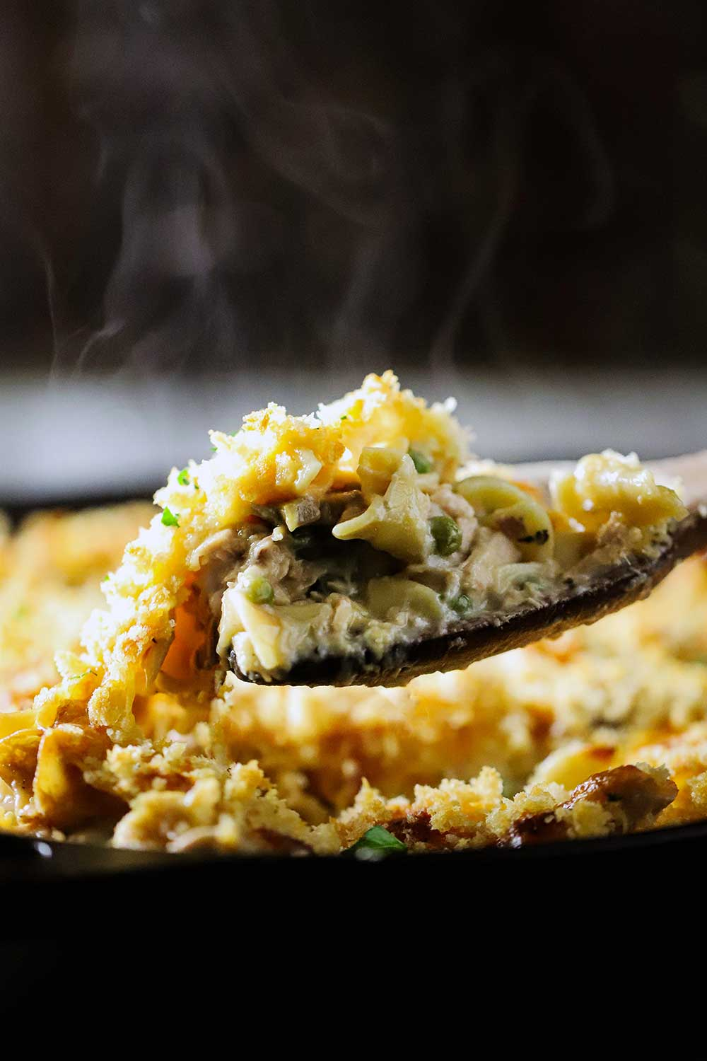A large wooden spoon lifting a helping of cooked tuna casserole out of a black cast-iron skillet.