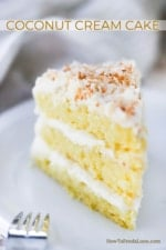 A 3-layered slice of coconut cream cake on a white dessert plate.