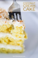 A fork inserted into the top of a piece of coconut cream cake standing upright on a white plate.