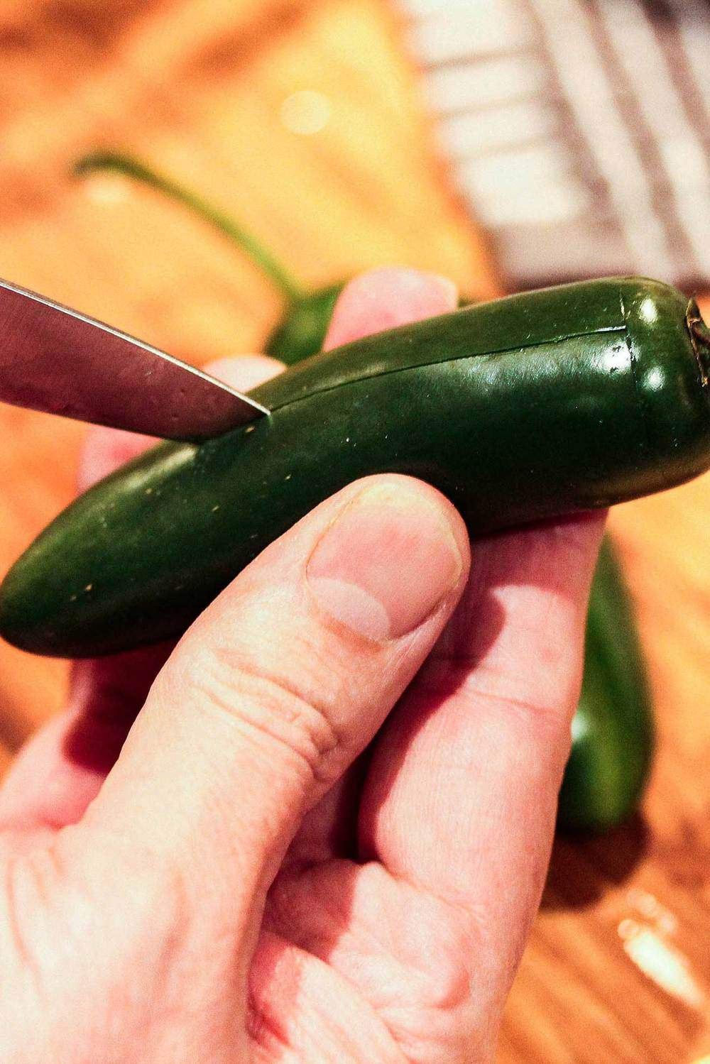 Knife slitting down a fresh Jalapeño