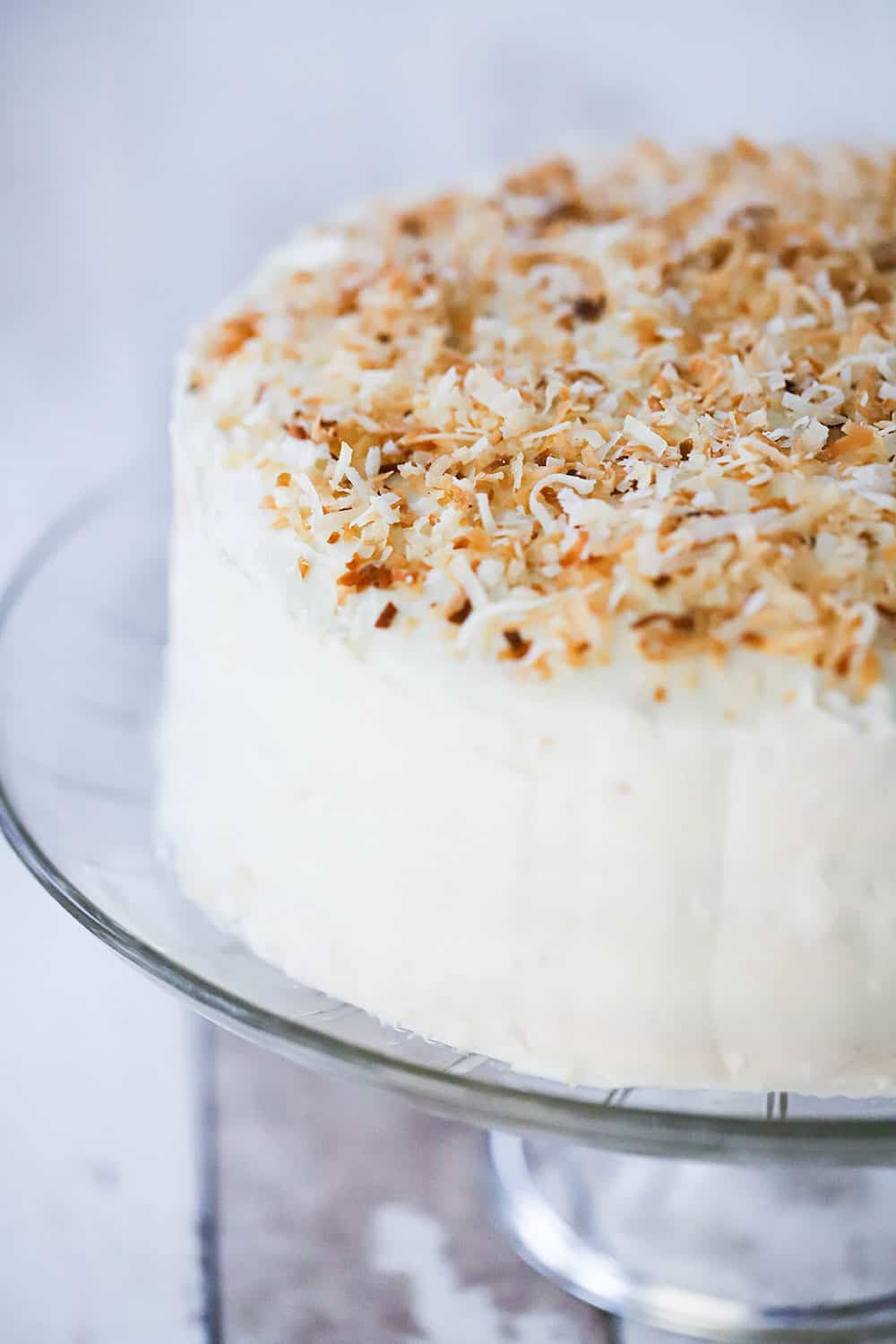 A coconut cream cake on a cake stand with toasted coconut flakes all over the top of the cake.