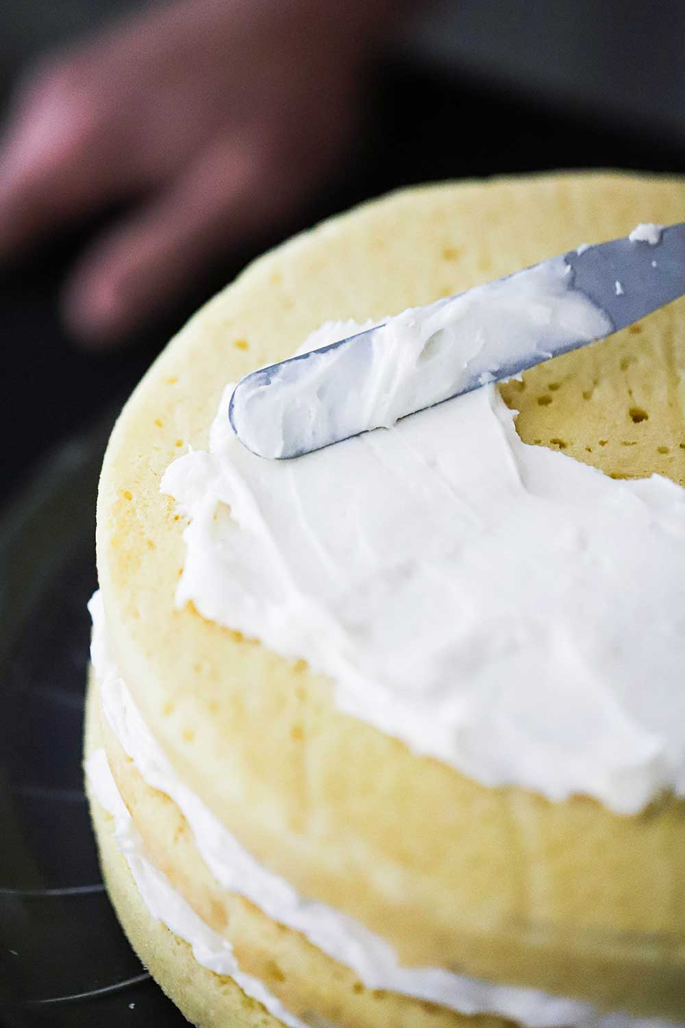 An off-set spatula smearing cream cheese frosting on a 3-layered yellow cake.
