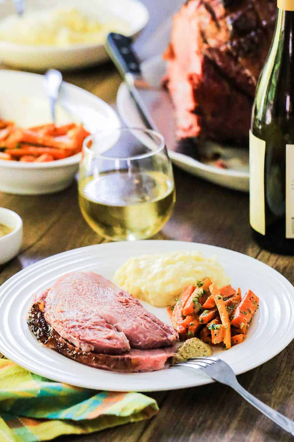 A white dinner plate with sliced ham, glazed carrots and mashed potatoes on it, next to a glass of white wine.