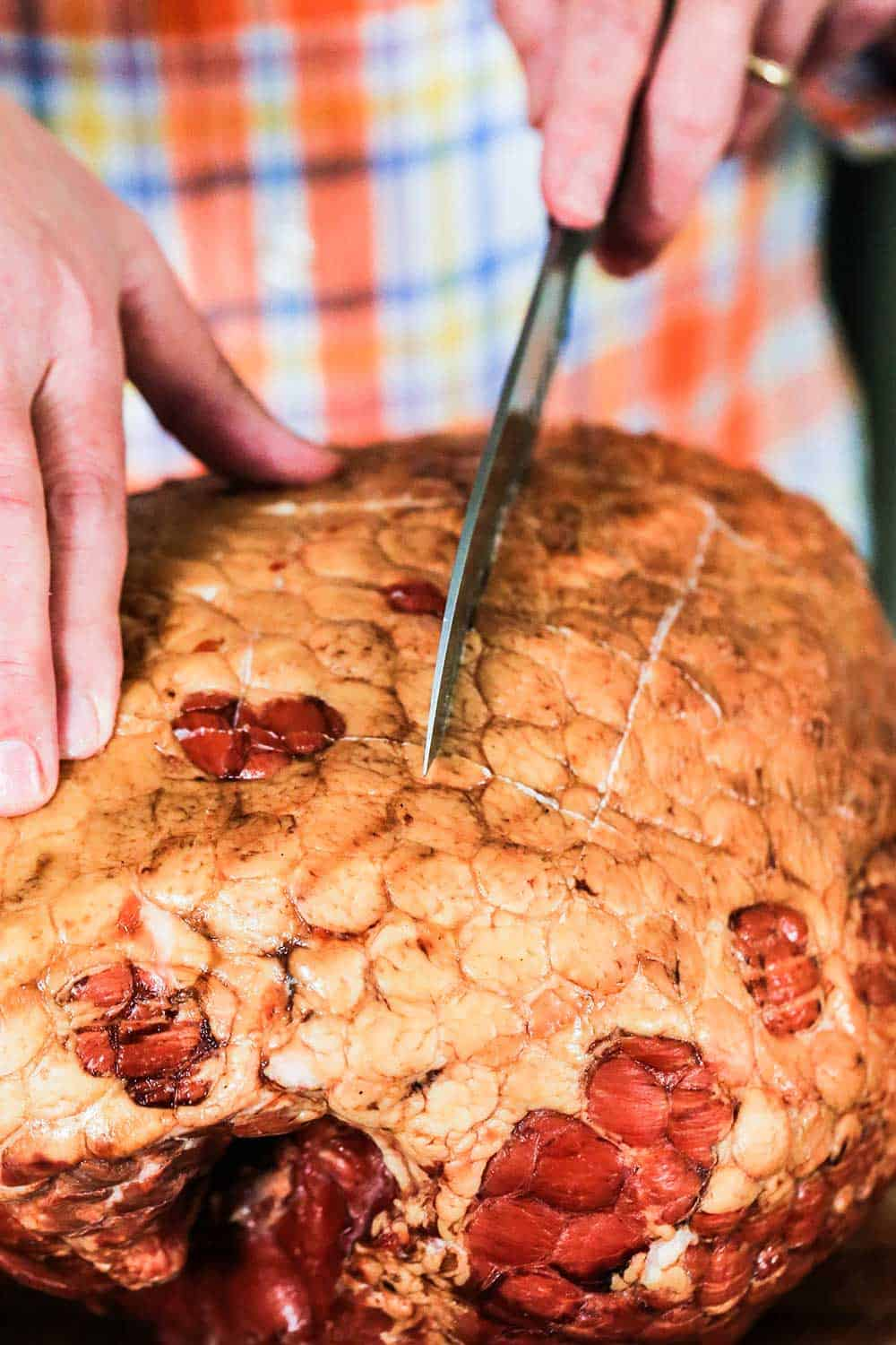Two hands using a large knife to score the fat cap of a smoked ham.