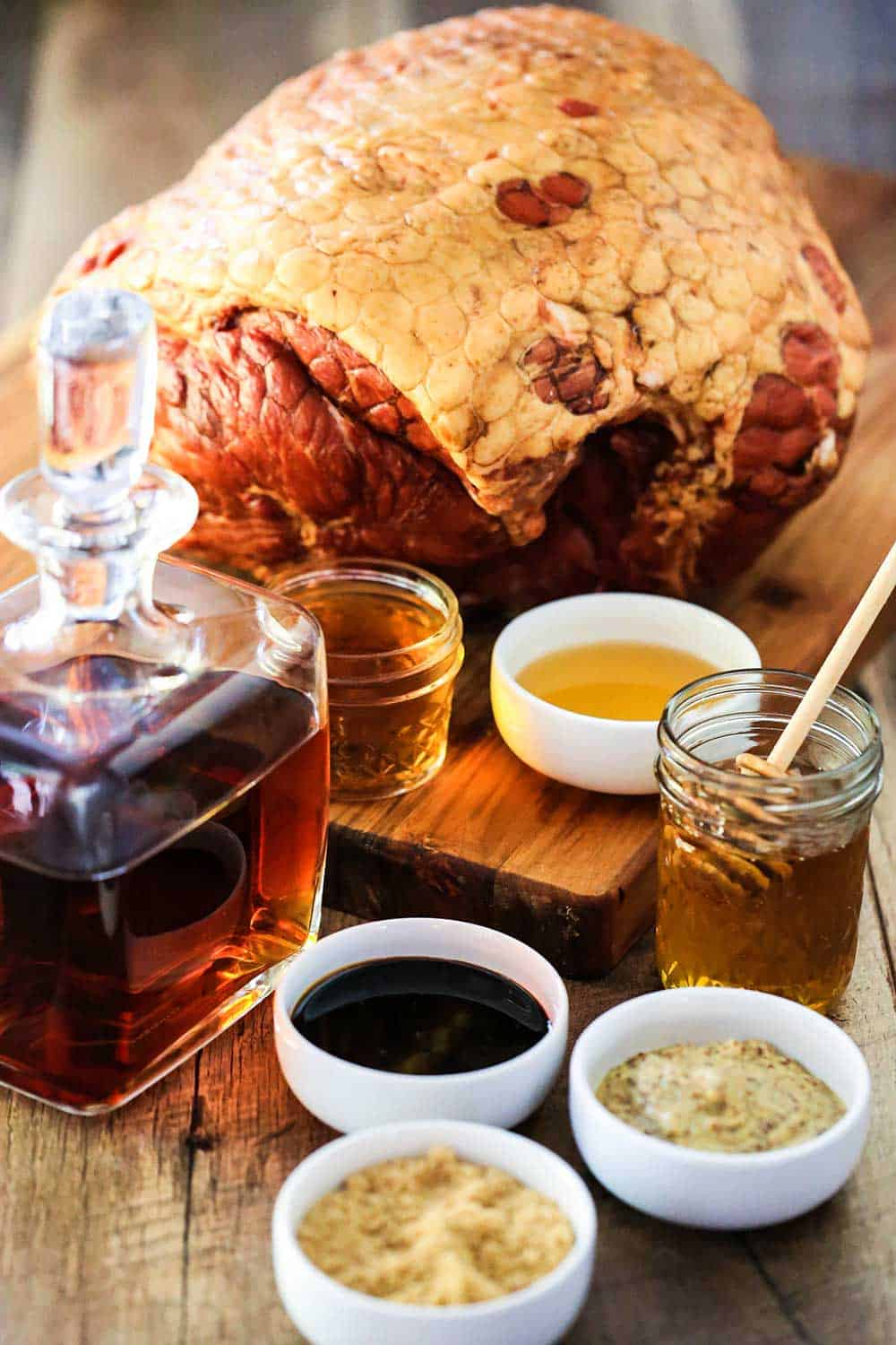 A cutting board with a large Berkshire ham in the background and a sniffer of bourbon, and small bowls of apple cider vinegar, mustard, and brown sugar next to it.