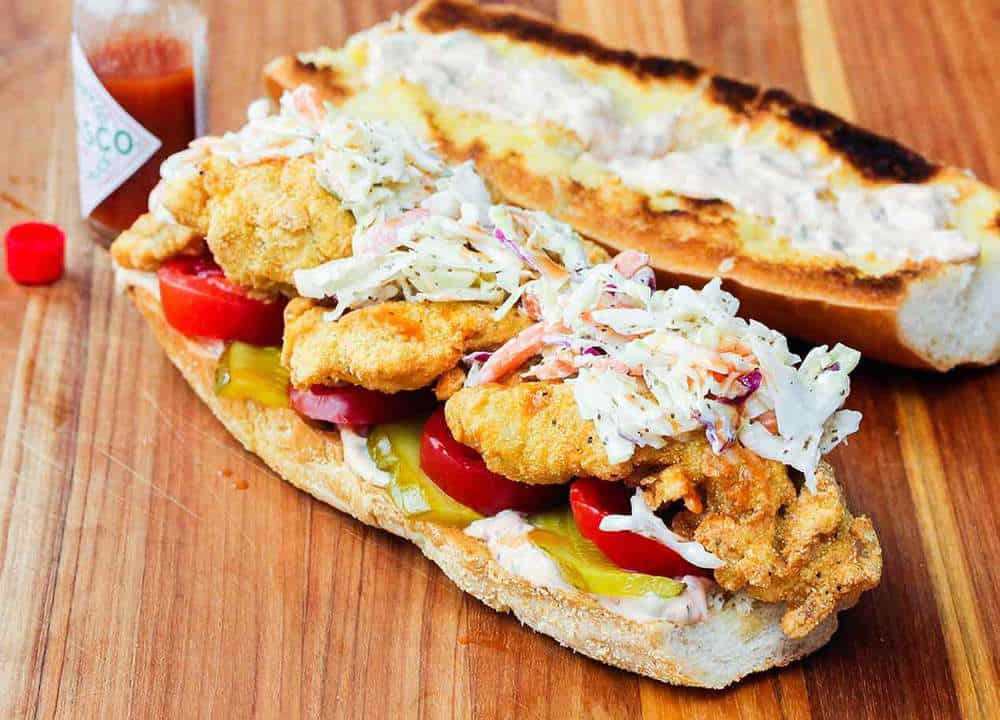Fried Catfish Po-Boy on a cutting board with a bottle of hot sauce next to it.