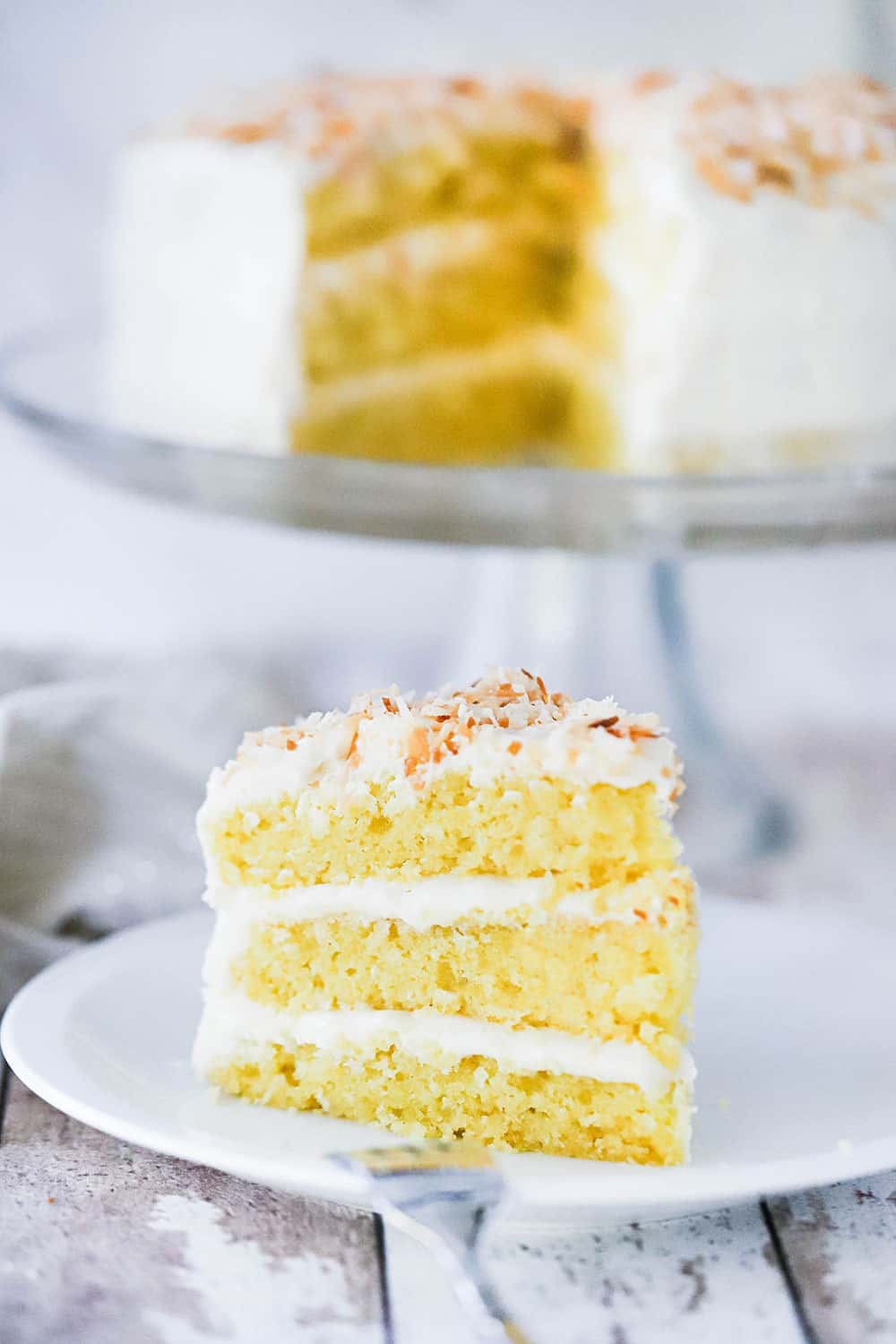 A 3-layered slice of coconut cream cake standing upright on a plate in front of the cake on a cake stand.