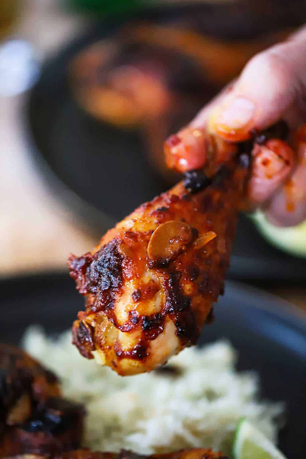 A hand, with a little sauce on the fingers, holding a roasted chipotle chicken leg up over a plate of cilantro-lime rice.