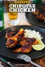 A black dinner plate filled with two pieces of roasted chipotle chicken, cilantro-lime rice, and 2 lime wedges, all sitting next to a glass of Mexican beer.