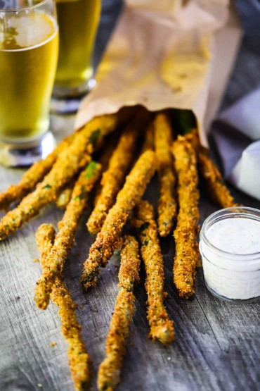 A pile of fried asparagus stalks pouring out of a paper bag.