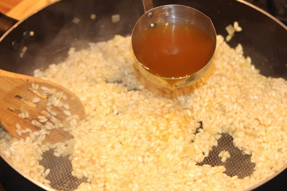 Add the hot stock a ladle or two at a time, and let it get absorbed before adding more