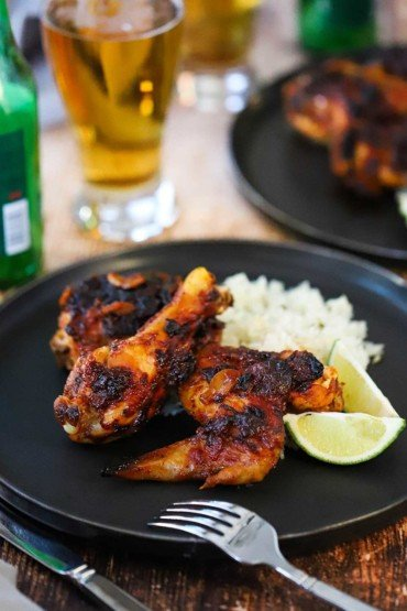 A black circular plate filled with two pieces of roasted chipotle chicken next to cilantro rice and lime wedges all next to a glass of beer.