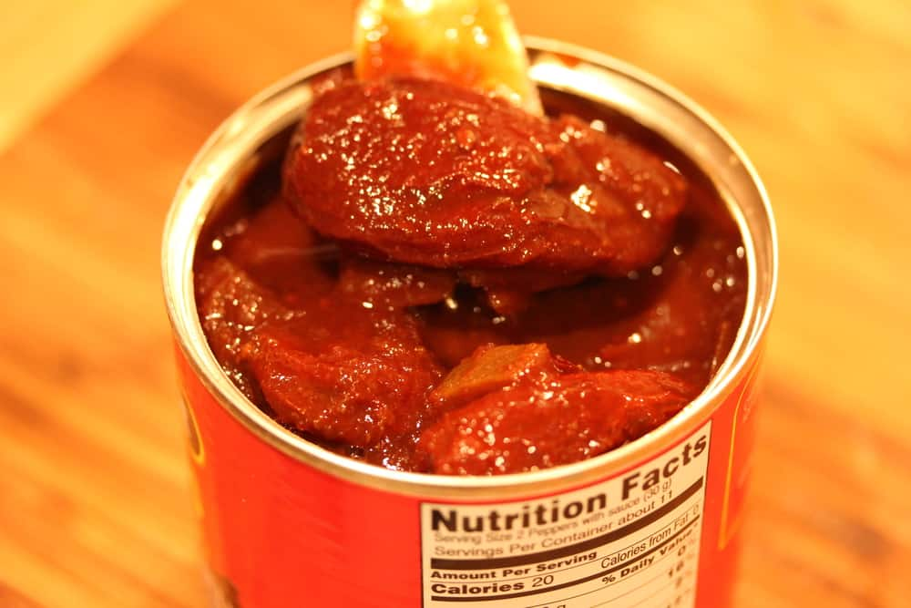 An opened can of chipotle chilis in adobo sauce on a wooden cutting board.