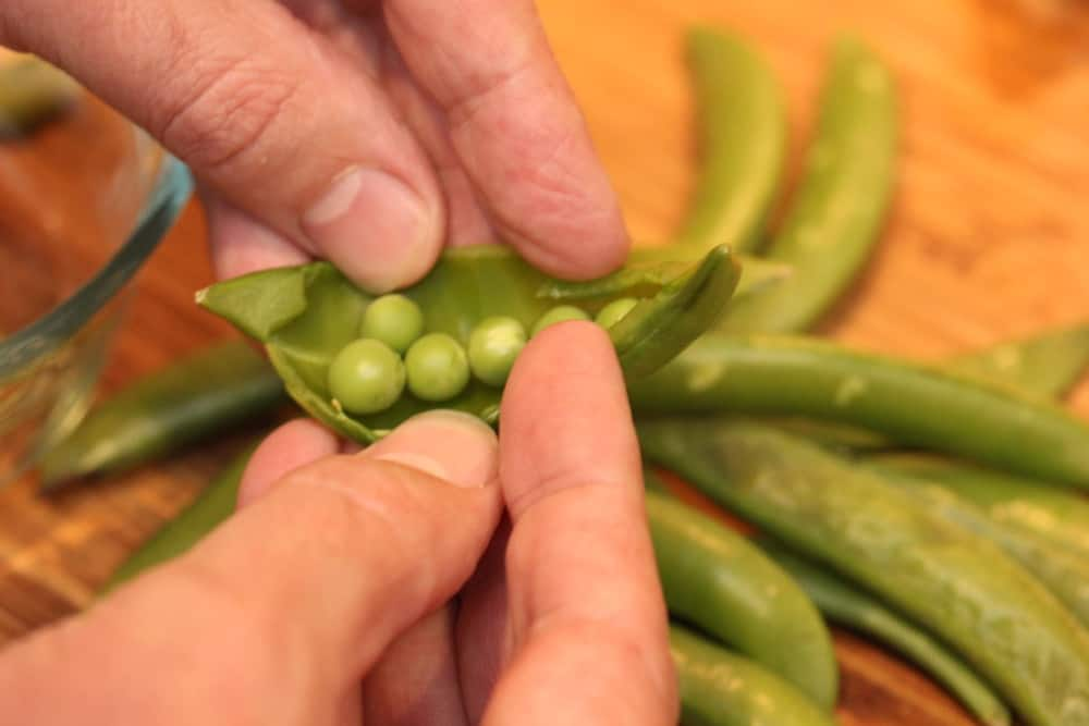 Hands removing peas from the skin next to peas on a wood cutting board