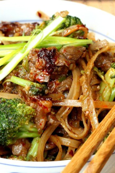 Beef & Broccoli Chow Fun in a white bowl with chopsticks