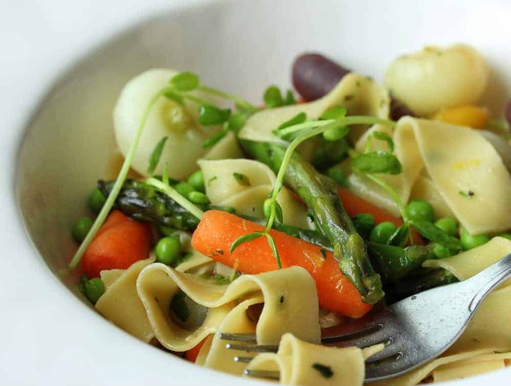 Pappardelle with Seasonal Veggies in a white bowl with a fork