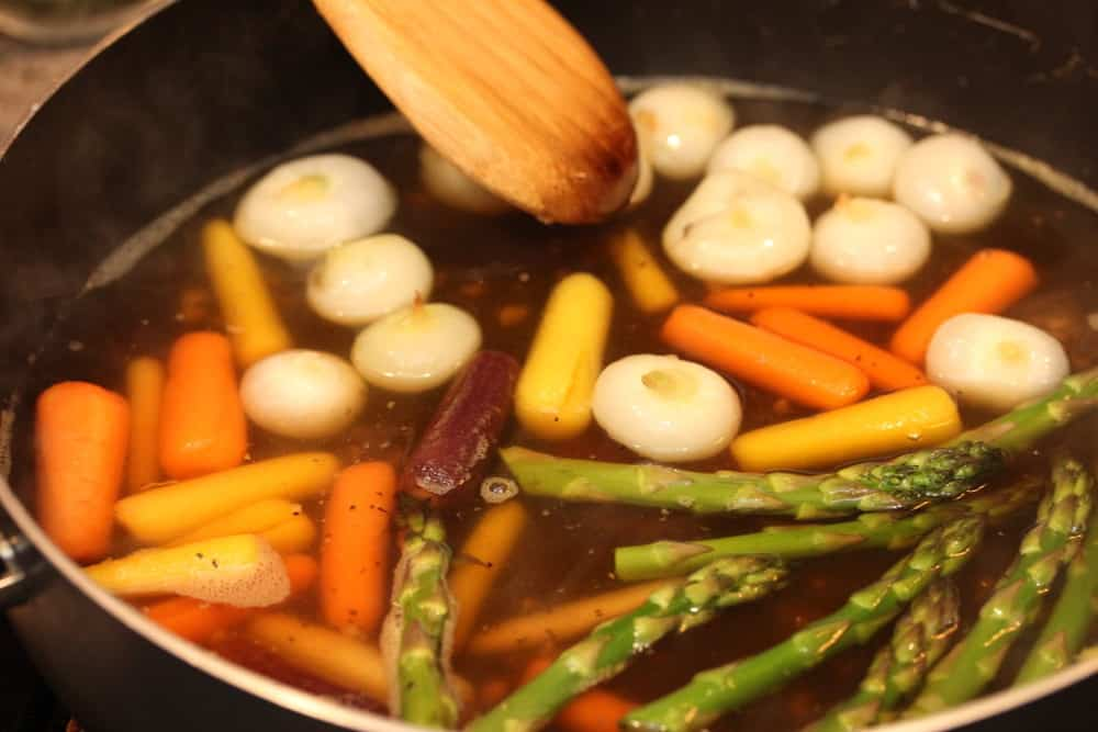 Veggies in stock in a black pan with a wood spoon