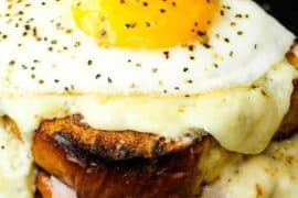 Croque Madame sandwich in a cast iron skillet with egg on top