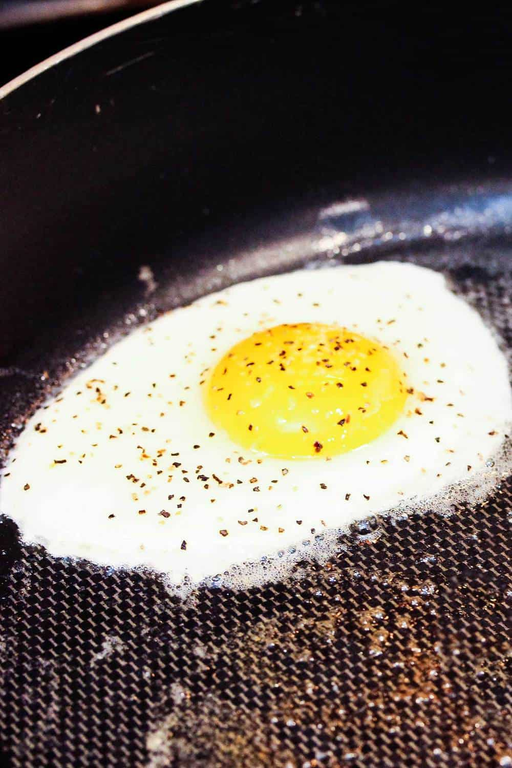 A sunny side up egg in a skillet for a Croque Madame
