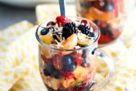 A large glass filled with summer fruit salad
