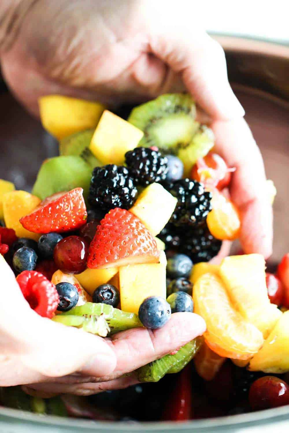 Two hands holding an assortment of berries and fruit for summer fruit salad