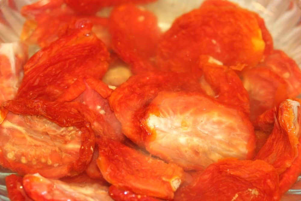 Re-hydrate the sun-dried tomatoes in a bowl of water