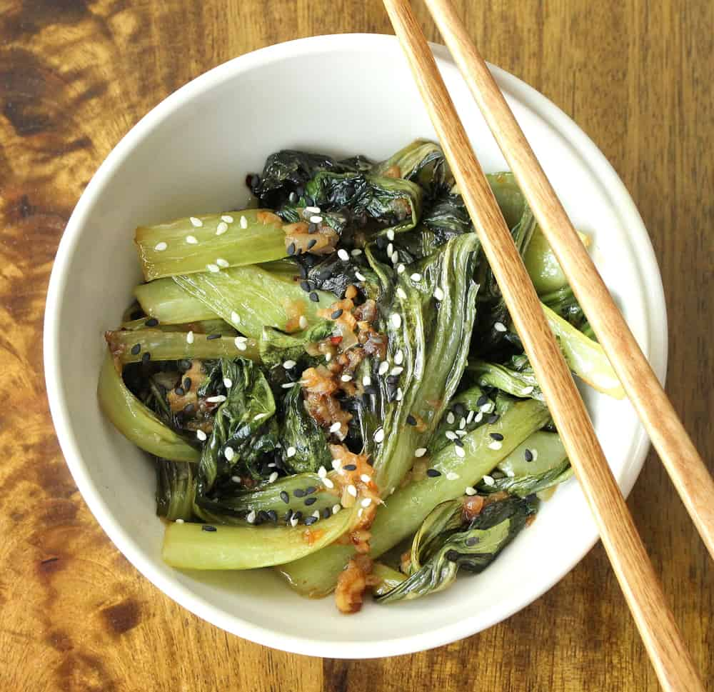 A white bowl holding sautéed baby bok choy with two chopsticks sitting on the side of the bowl.