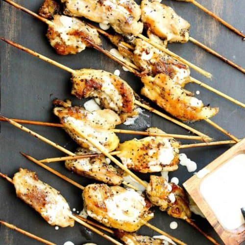 Grilled chicken skewers with Alabama white sauce drizzled all over.