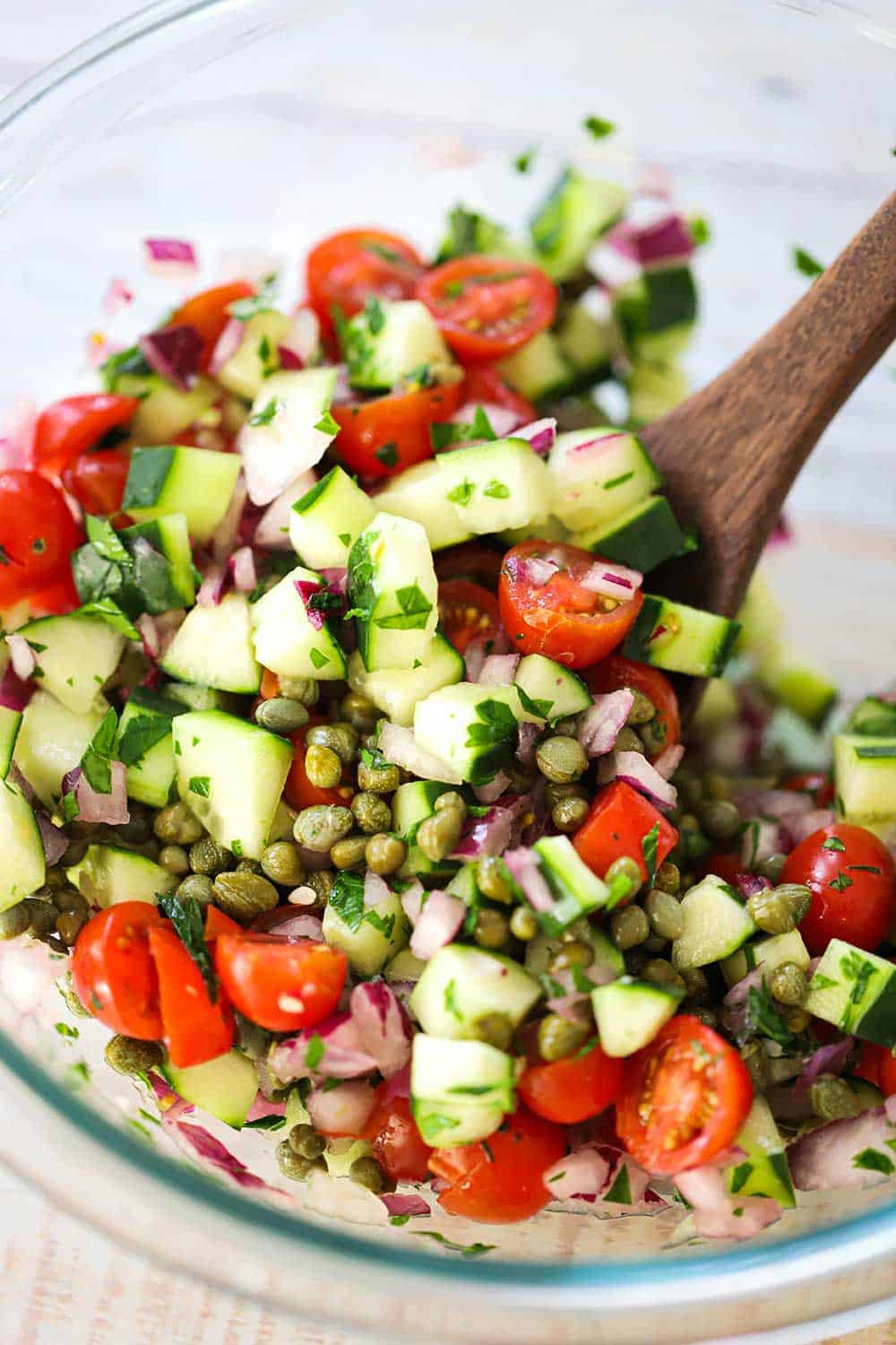 A glass bowl containing a mix of chopped tomatoes, cucumbers, capers, olives, and herbs with a wooden spoon in the middle of it.